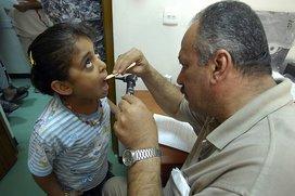 Us_navy_080828-n-0292s-005_an_iraqi_doctor_checks_a_child_s_throat_during_an_examination_at_a_free_health_clinic_during_a_combined_medical_event_for_local_iraqi_families
