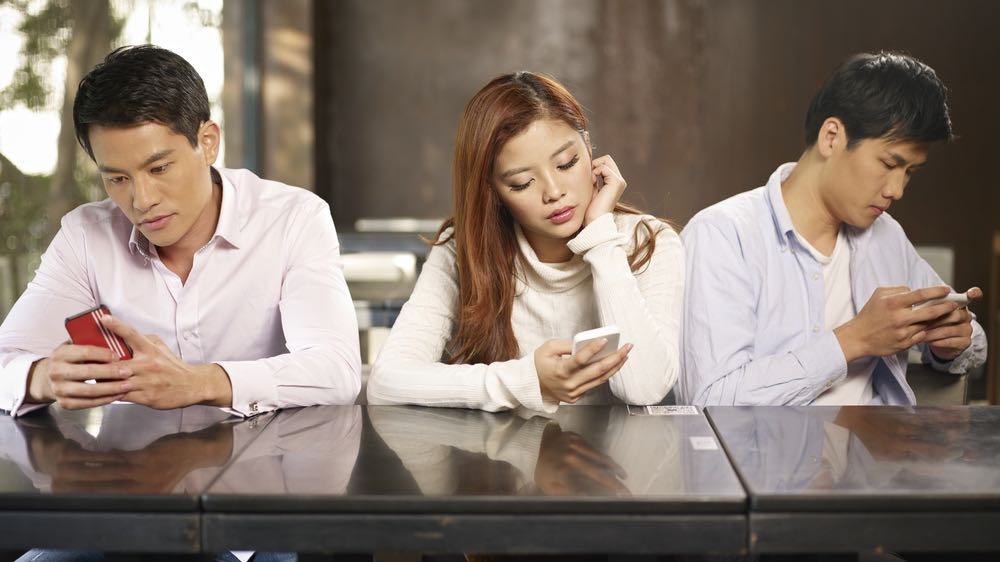 Young people ignoring each other with smartphones.