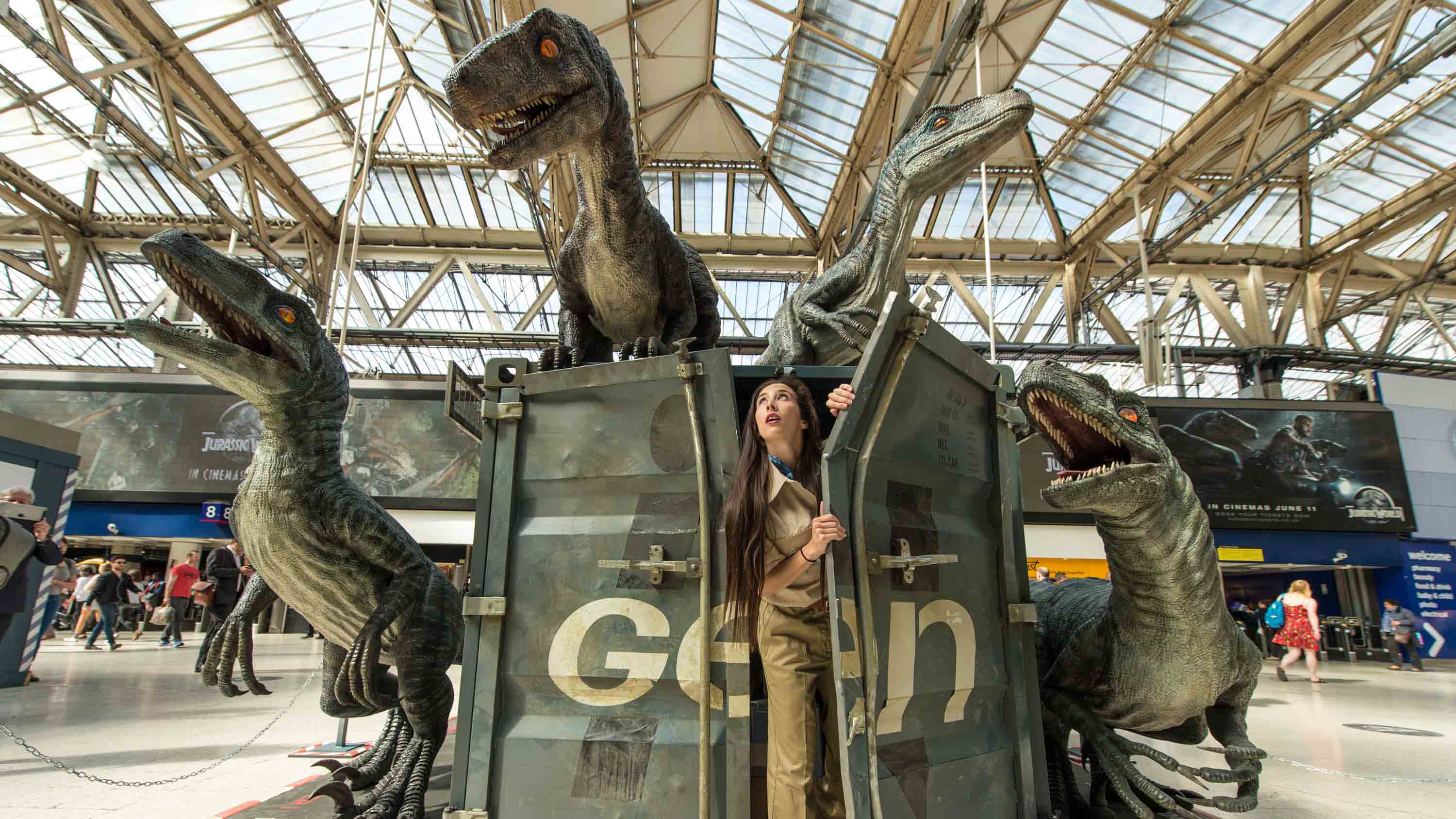 A dinosaur attendant emerges from a shipping container surrounded by dinosaurs during the 'Jurassic World'.