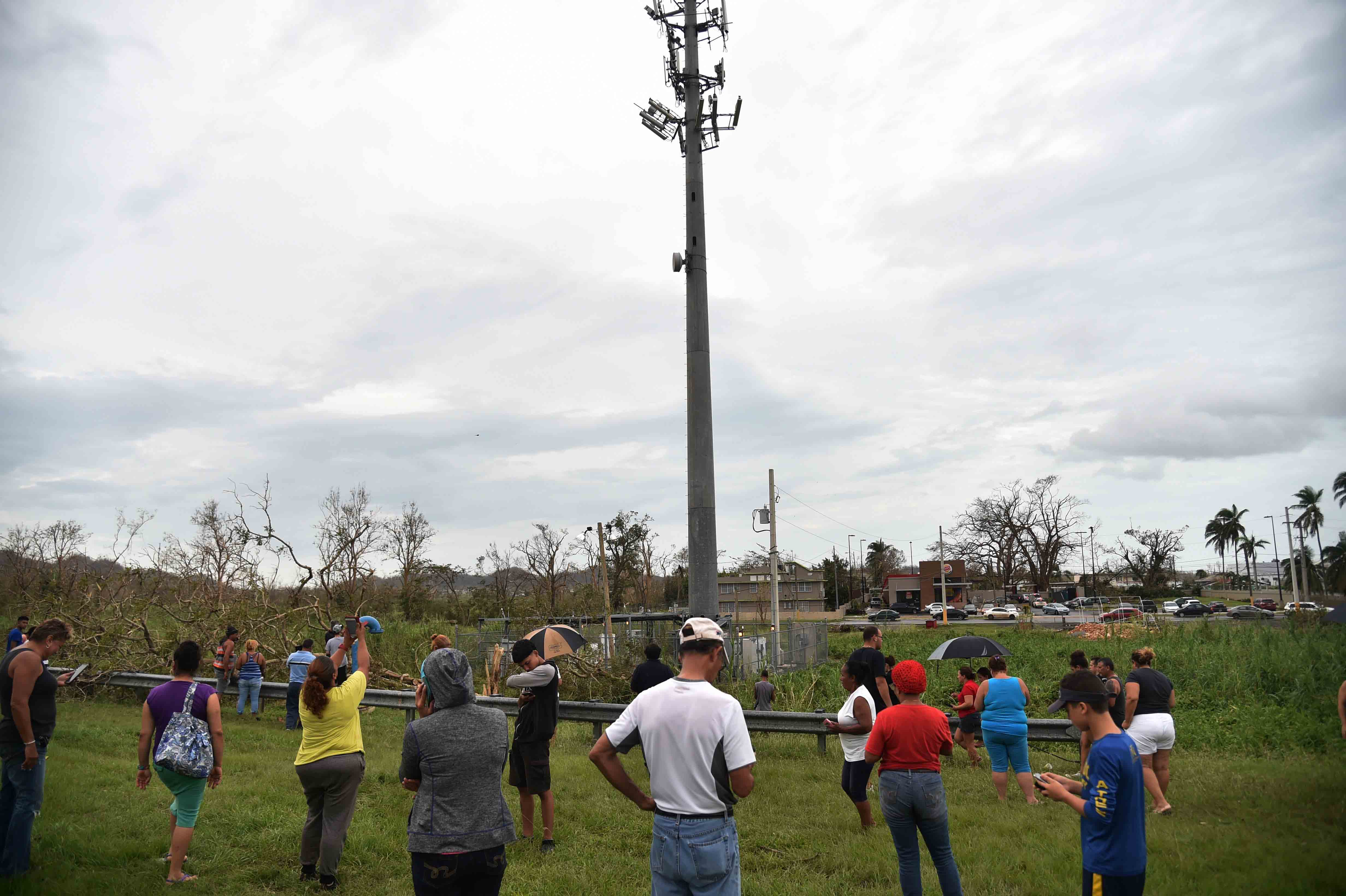 People try to get a signal before a celular communications tower on the expressway in Dorado, Puerto Rico, on September 22, 2017 in the aftermath of Hurricane Maria.