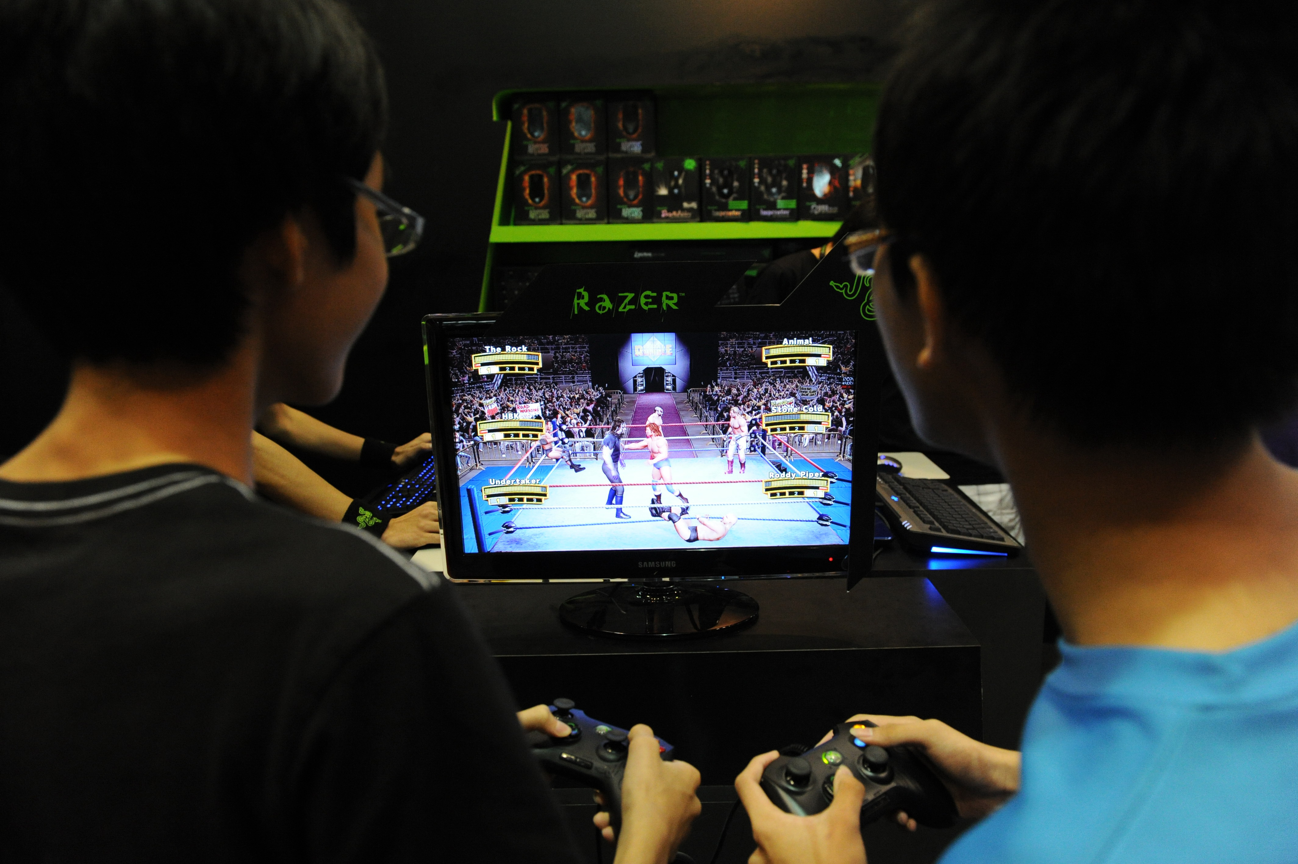 This photo taken on March 11, 2011 shows two boys slugging it out in an Xbox 360 wrestling game at the IT Show 2011 in Singapore. (ROSLAN RAHMAN/AFP/Getty Images)