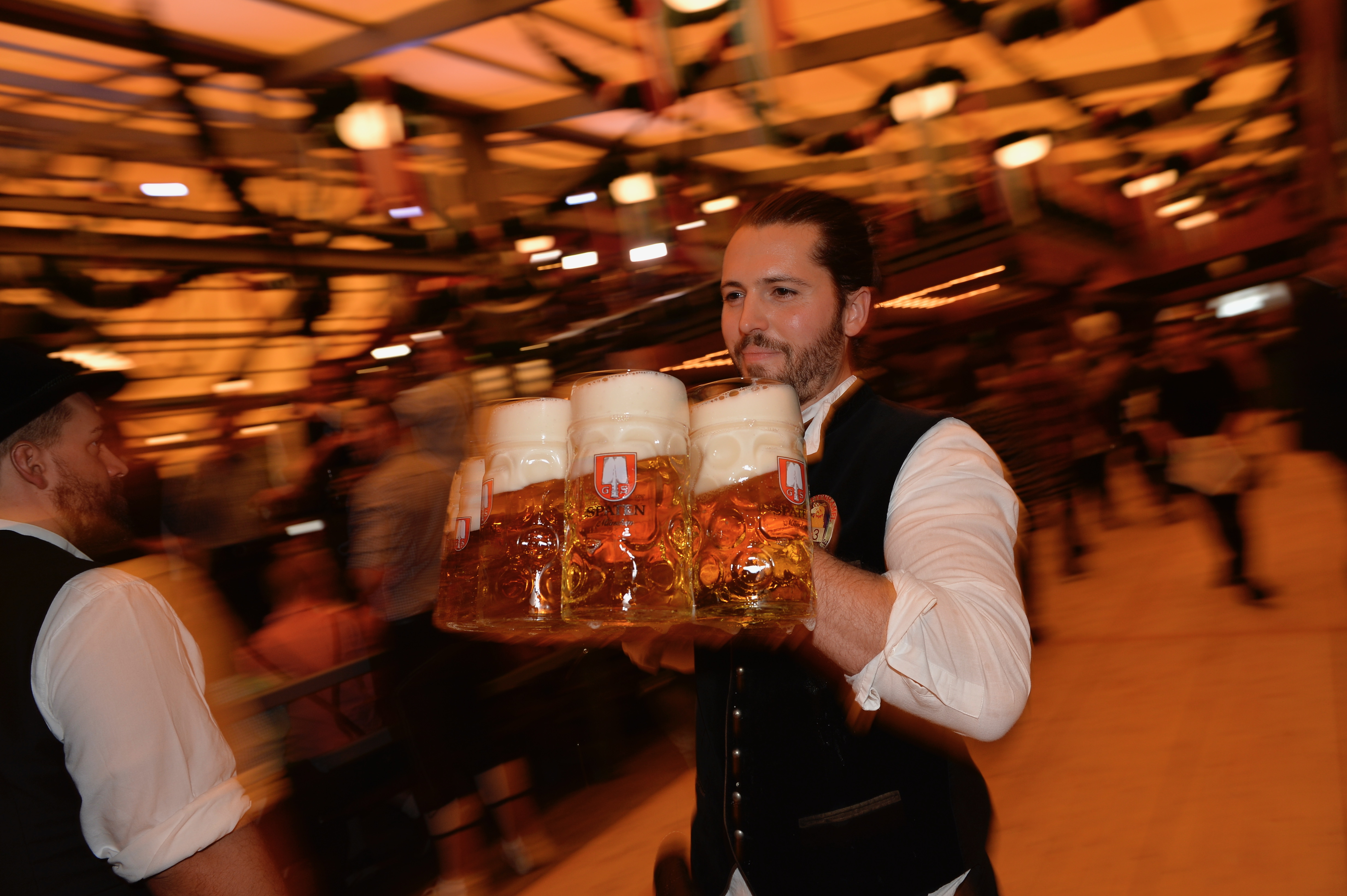 A waiter serves beer mugs after the official opening of the 184th Oktoberfest, Munich's annual beer festival, on September 16, 2017 in Munich, southern Germany. (Photo credit GUENTER SCHIFFMANN/AFP/Getty Images)